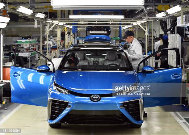 """Employees of Toyota Motors check the FCV """"Mirai"""" on its final assembly line during the vehicle's line off ceremony at the Motomachi factory in Toyota..."""