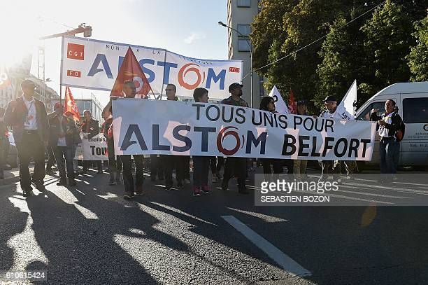 Employees of trainbuilding giant Alstom walk towards the headquarters of Alstom in the Paris suburb of SaintOuen on September 27 behind a banner...
