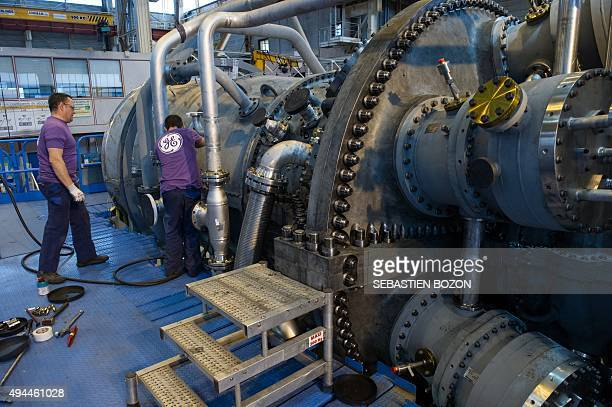 Employees of US multinational General Electric work on a gas turbine at the GE plant in Belfort eastern France on October 27 2015 AFP PHOTO /...