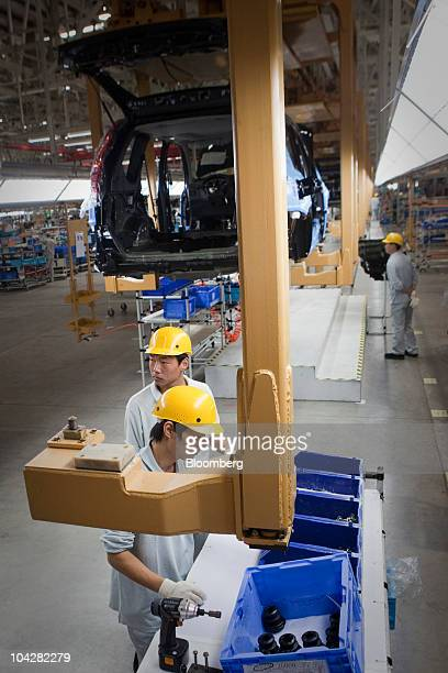 Employees of Zhengzhou Nissan Automobile Co Ltd work on the assembly line of the XTrail sport utility vehicle in Zhengzhou Henan province China on...