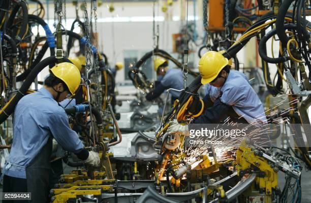 Employees on the assembly line produce cars in Mazda's 'Family' line of vehicles at China First Automobile Works Group Haima Automobile Co Ltd April...