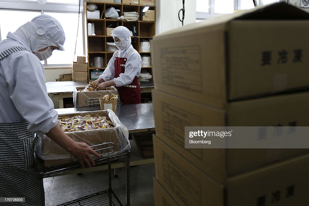 Employees open boxes filled with sachets of seasoning sauce and mustard to accompany packets of fermented soybeans, known as natto, at the Matsushita Shoten Y.K. production facility in Kawasaki, Kanagawa Prefecture, Japan, on Friday, June 7, 2013. From Japan's natto makers and operators of neighborhood baths to its largest refiner and utilities, the weaker yen offers domestically focused industries nothing to offset higher import prices. Photographer: Kiyoshi Ota/Bloomberg via Getty Images