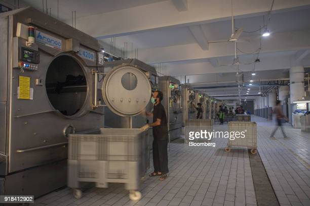 Employees operate Brongo Srl L4200 industrial washing machines in the washing unit of the Artistic Denim Mills Ltd factory in Karachi Pakistan on...