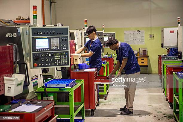 Employees operate machinery at the Coway Engineering Marketing Pte manufacturing facility in Singapore on Wednesday Oct 1 2014 Coways Singapore...