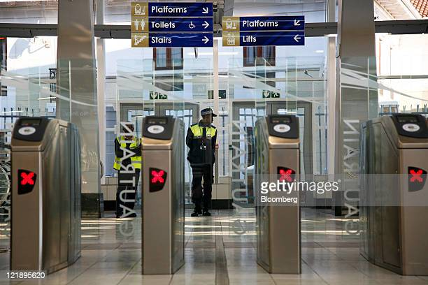 Employees oversee the electronic ticket gates at Gautrain's Hatfield mass transit rail station in Pretoria South Africa on Monday Aug 22 2011 South...