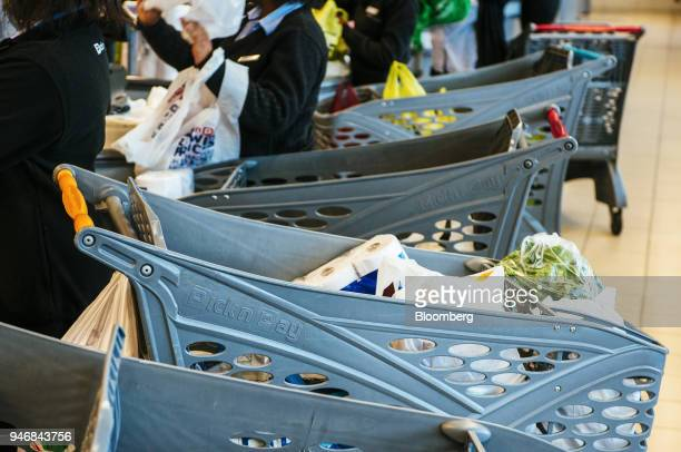 Employees pack bags of shopping into branded shopping carts at the check out area inside a Pick n Pay Stores Ltd supermarket in Johannesburg South...