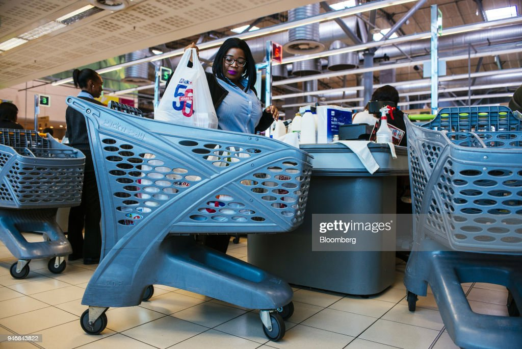 Employees pack bags of shopping into branded shopping carts at the check out area inside a Pick n Pay Stores Ltd. supermarket in Johannesburg, South Africa, on Monday, April 9, 2018. As trade tensions and the Syrian conflict roiled markets this month, South Africas rand has been stuck in an unusually narrow range for one of the worlds most volatile currencies. Photographer: Waldo Swiegers/Bloomberg via Getty Images