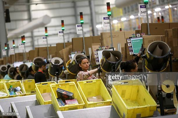 Employees pack boxes of merchandise at an Amazoncom Inc fulfillment center in Peterborough UK on Tuesday Nov 15 2016 The online retail giant needs...
