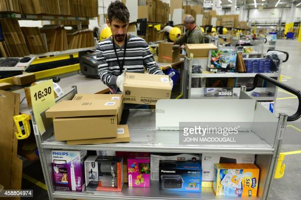 Employees pack goods for shipment at US online retail giant Amazon's Brieselang logistics center west of Berlin on November 11 2014 The center is one...
