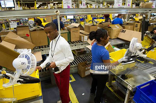 Employees pack items to be shipped from the Amazoncom Inc distribution center in Phoenix Arizona US on Monday Nov 26 2012 US retailers are extending...