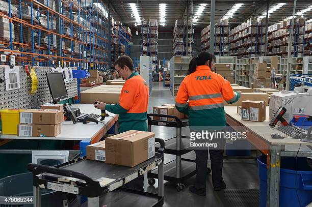 Employees pack products into boxes at Toll Holdings Ltd's distribution warehouse for Newell Rubbermaid Inc in Melbourne Australia on Friday May 29...