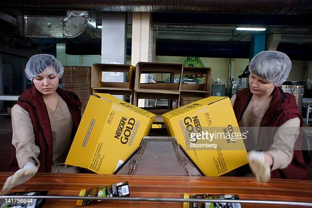 Employees pack sachets of Nescafe Gold coffee into boxes at Nestle SA's Svitoch factory in Lviv Ukraine on Thursday March 22 2012 Switzerland's...