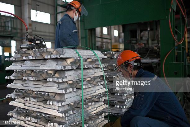 Employees package aluminum ingots at the China Hongqiao Group Ltd aluminum smelting facility in Zouping China on Monday Nov 4 2013 China Hongqiao...