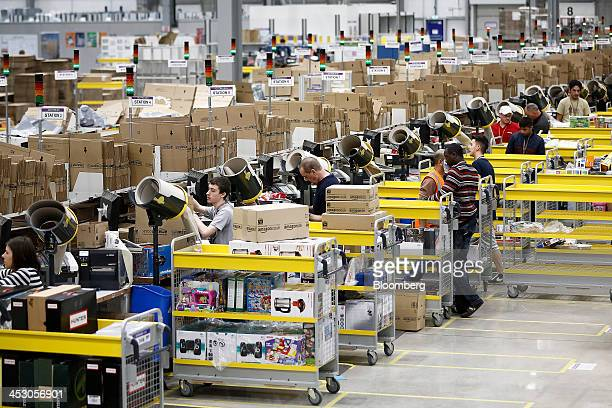 Employees package customer orders ahead of shipping at one of Amazoncom Inc's fulfillment centers in Rugeley UK on Monday Dec 2 2013 Online retailers...