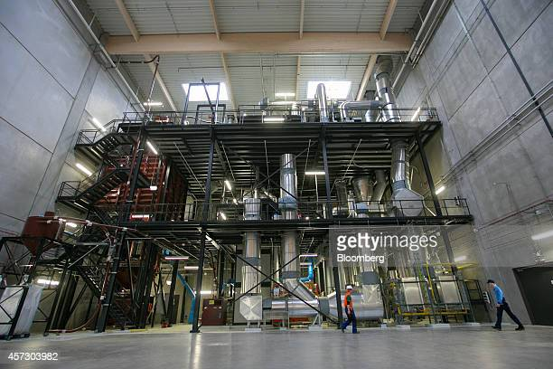Employees pass a coffee bean roaster as it stands in a hall at the Nestle SA factory in Schwerin Germany on Thursday Oct 16 2014 The factory one of...