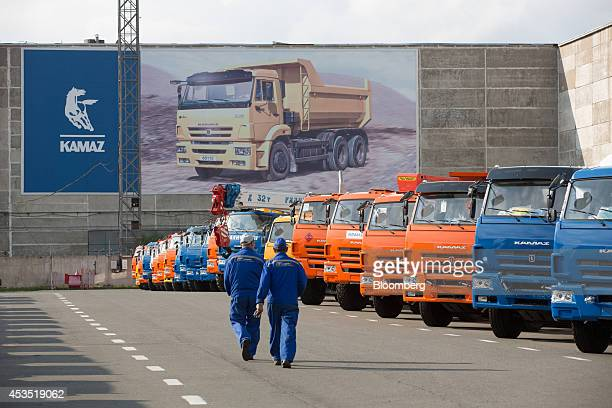 Employees pass a long line of completed heavy trucks awaiting distribution outside the OAO KamAZ plant in Naberezhnye Chelny Russia on Monday Aug 11...
