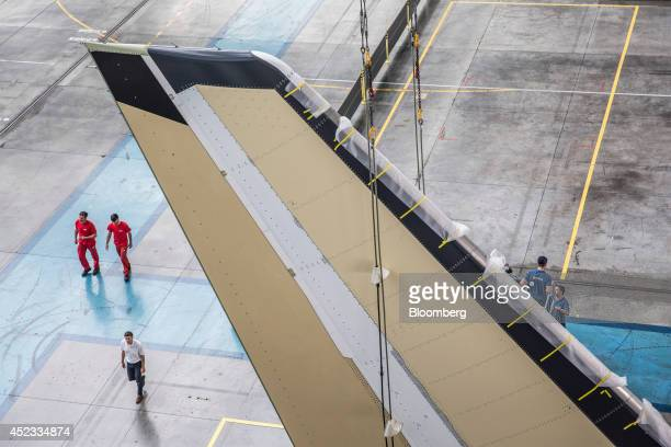 Employees pass beneath a tail fin for an Airbus A330 aircraft as it sits on the assembly line in the Airbus Group NV factory in Toulouse France on...