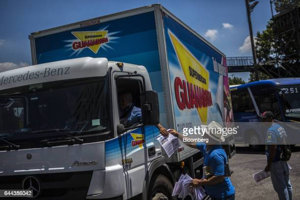 Employees pass out pamphlets to passing vehicles during a protest against the privatization of the State's water and sewage utility in front of Cia...