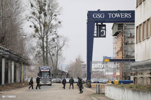 Employees pass the GSG Towers Sp. Z o.o. Factory signage, a unit of the Gdansk Shipyard Group, in Gdansk, Poland, on Wednesday, March 28, 2018....