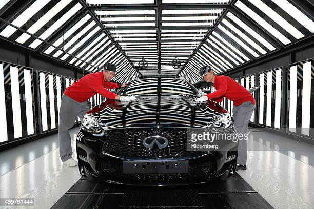 Employees perform a quality inspection on an Infiniti Q30 automobile on the production line at the Nissan Motor Co production plant in this arranged...