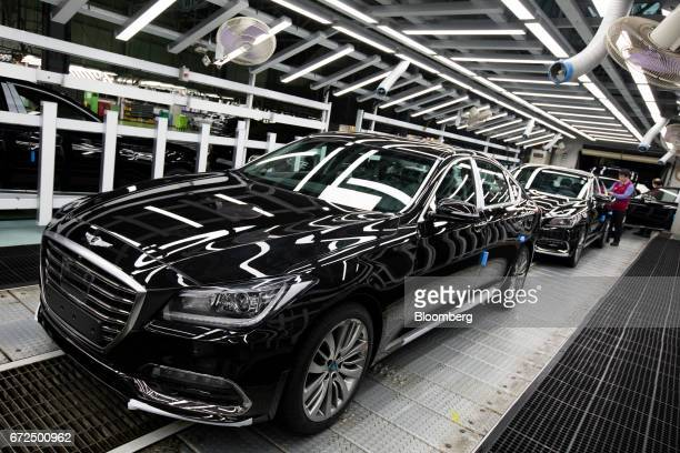Employees perform final inspections on Hyundai Motor Co Genesis luxury sedans on the production line at the company's plant in Ulsan South Korea on...