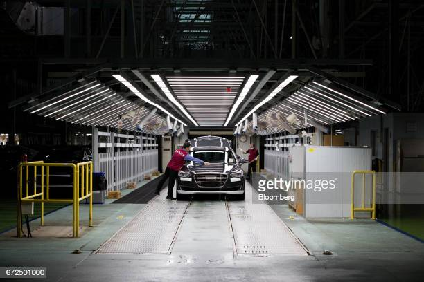 Employees perform final inspections on Hyundai Motor Co. Genesis luxury sedans on the production line at the company's plant in Ulsan, South Korea,...