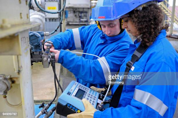 Employees perform maintenance on a machine at the Air Liquide factory in Moissy Cramayel France on Friday Feb 13 2009 Air Liquide SA the world's...