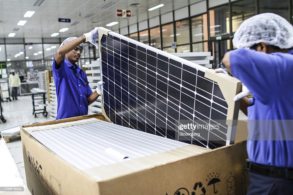 Employees place a solar panel into a box at the Tata Power Solar Systems Ltd. manufacturing plant in Bangalore, India, on Tuesday, June 11, 2013. Tata Groups solar unit is expanding its business building plants for customers, forecasting that offices and factories will be paying more for grid power than solar by 2016 in most Indian states. Photographer: Dhiraj Singh/Bloomberg via Getty Images