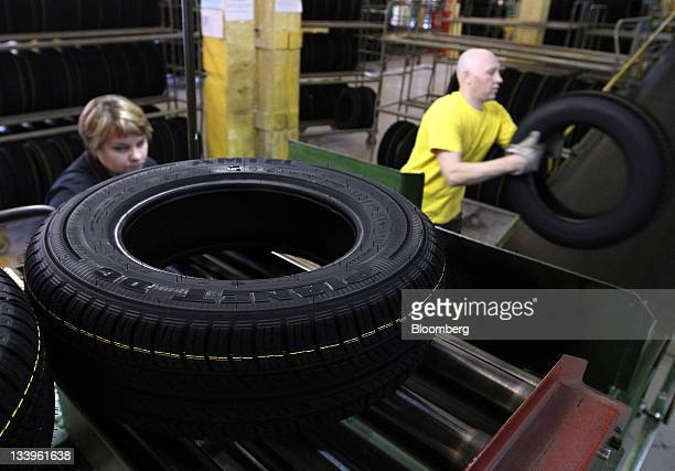 Employees place completed car tires onto racks at the ZAO Sibur Holding tire manufacturing plant in Voronezh, Russia, on Friday, Nov. 18, 2011....
