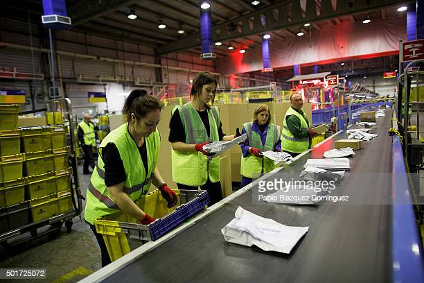 Employees place parcels on to a conveyor belt at a Correos CAM 'Mass Admission Centre' in Vallecas on December 16 2015 in Madrid Spain Christmas...