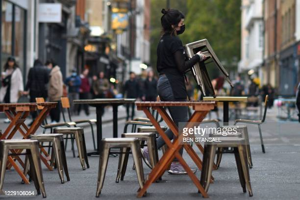 Employees place tables outside their restaurant in preparation for evening business, on Frith Street, Soho in the West End of London on October 16 as...