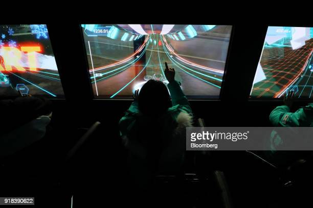 Employees play a video game onboard an autonomous 5G connected bus operated by KT Corp as it travels along a road during a media event in Gangneung...