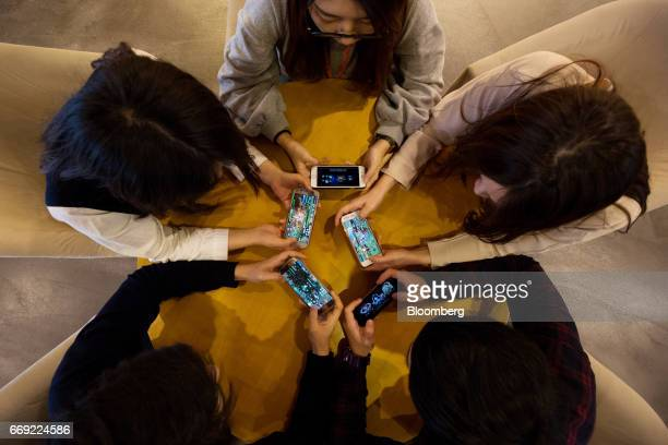 Employees play mobile games on smartphones in the cafeteria at the Netmarble Games Corp headquarters in Seoul South Korea on Friday April 14 2017...