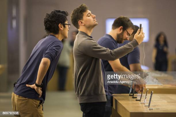 Employees play with the new facial recognition feature of the iPhone X the morning of its release at the Georgetown Apple Store in Washington USA on...