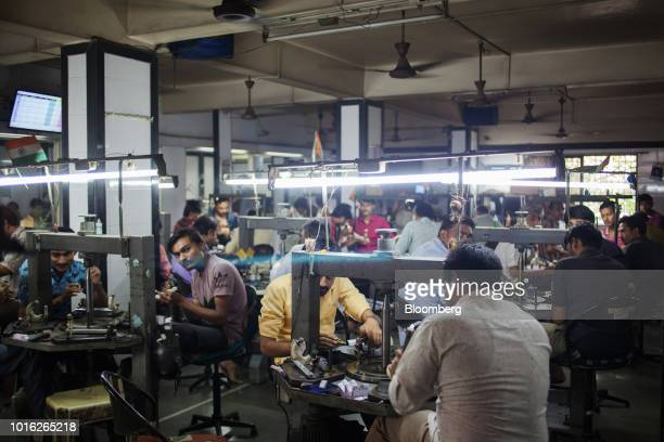 Employees polish diamonds at a Virani Gems workshop in Surat Gujarat India on Thursday Aug 9 2018 Diamond jewelry demand rose to a record $82 billion...