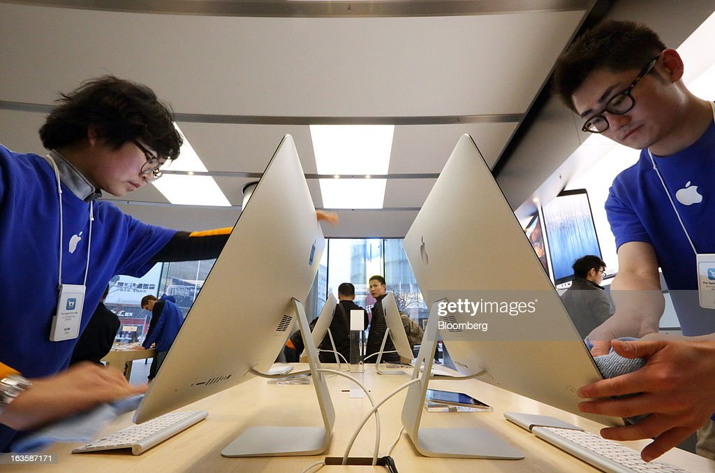 Employees polish the monitors of Apple Inc.'s Mac Pro desktop computers at the company's store in the Wangfujing area of Beijing, China, on Tuesday, March 12, 2013. Apple's Wangfujing store is the largest in Asia. Photographer: Tomohiro Ohsumi/Bloomberg via Getty Images
