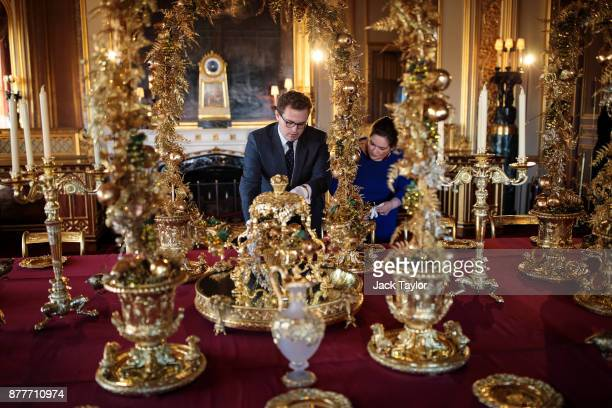 Employees pose by the table in the State Dining Room which has been decorated for the Christmas period with silvergilt pieces from the Grand Service...