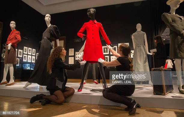 Employees pose in front of a red dress coat by Valentino Couture spring/summer 1971 with a reserve price of £10001500 during a preview of Audrey...