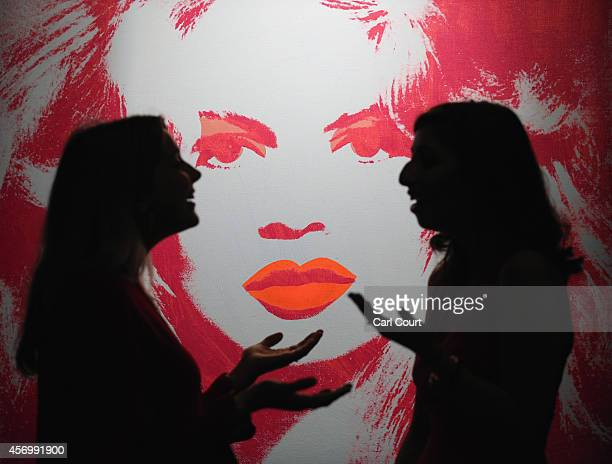 Employees pose next to a painting by Andy Warhol entitled 'Brigitte Bardot' during a press preview at Sotheby's on October 10, 2014 in London,...