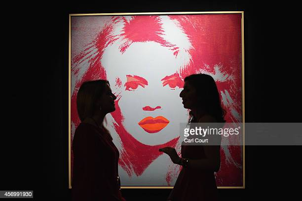 Employees pose next to a painting by Andy Warhol entitled 'Brigitte Bardot' during a press preview at Sotheby's on October 10 2014 in London England...