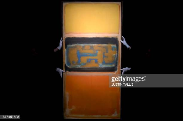 Employees pose with an artwork by American artist Mark Rothko entitled 'No 1' with an estimated price of 812 million GBP during a photocall ahead of...