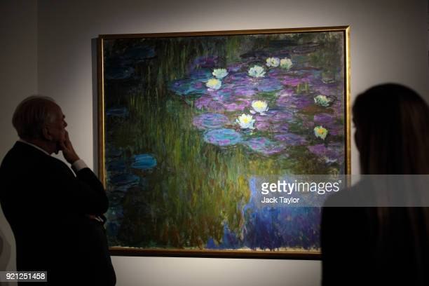 Employees pose with 'Nympheas en fleur' by Claude Monet during a photocall for the Peggy and David Rockefeller art collection at Christies auction...