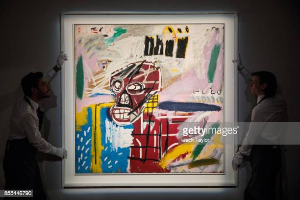 Employees pose with 'Red Skull' 1982 by JeanMichel Basquiat at Christie's London on September 29 2017 in London England Christie's Auction House is...
