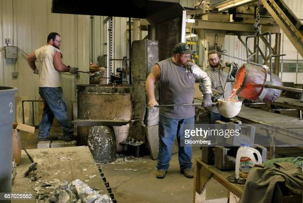 Employees pour melted aluminum while working in the foundry at the Super Vac Manufacturing Co production facility in Fort Collins Colorado US on...