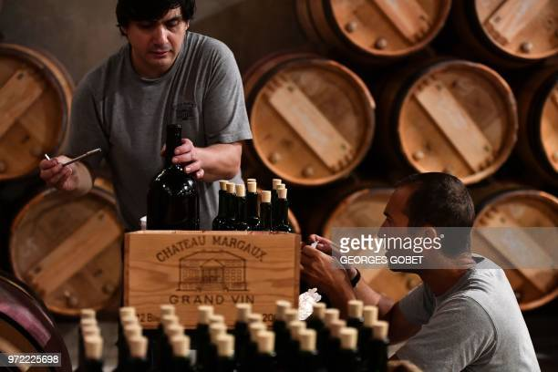 Employees pour wine into bottles and label boxes as they prepare samples in the wine cellar of Chateau Margaux on June 11 2018 in Margaux near...
