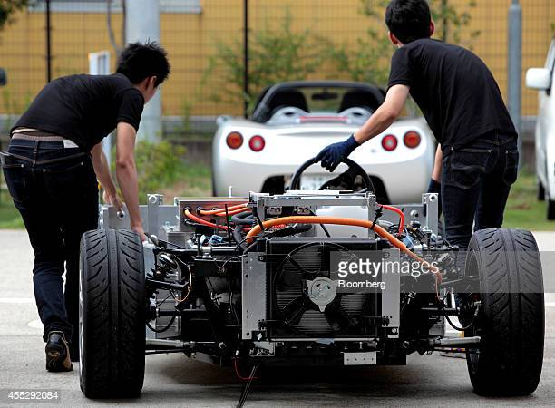 Employees prepare a bodiless GLM Co Tommykaira ZZ electric vehicle for a test drive at the company's RD facility in Uji Kyoto Prefecture Japan on...
