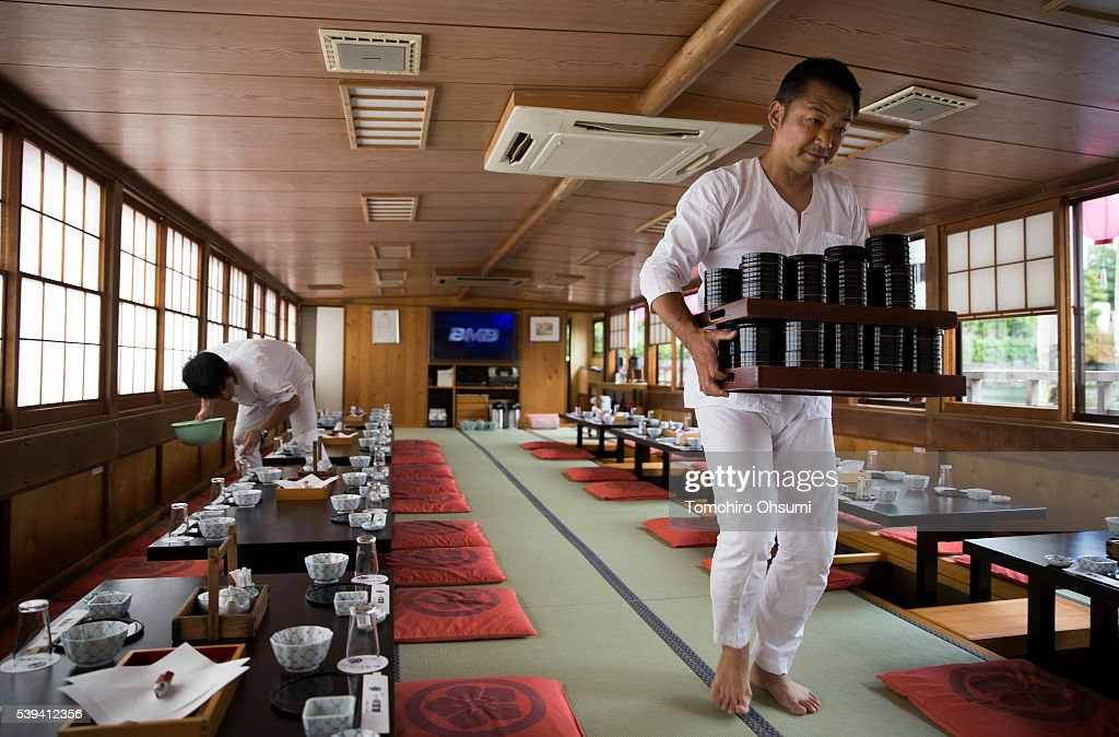 Employees prepare before a yakatabune, or traditional low barge style boat, operated by Mikawaya shipping agent, departs the pier on June 11, 2016 in Tokyo, Japan. About 35 companies operate over 100 yakatabune boats in Tokyo offering services such as dinner or karaoke inside the boats while cruising in Tokyo's bay area, according to the Tokyo Yakatabune Association.