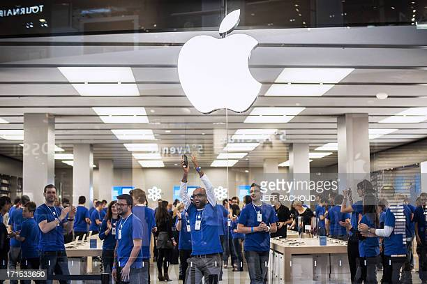 Employees prepare before the opening of the newly Apple store inside the Confluence shopping centre in Lyon on the day of its inauguration on April 4...