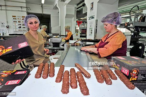 Employees prepare Nestle SA kingsize 'Lion' chocolate bars ahead of packaging at the company's Svitoch factory in Lviv Ukraine on Thursday March 22...