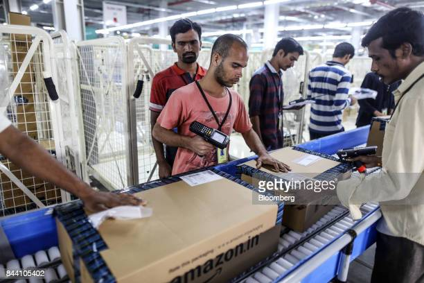 Employees prepare packages for shipment on the conveyor belt at the Amazoncom Inc fulfillment center in Hyderabad India on Thursday Sept 7 2017...